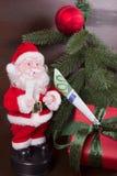 Santa Claus med gåvan av pengar Arkivbilder