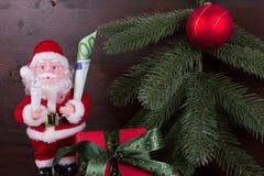 Santa Claus med gåvan av pengar i hans hand Royaltyfria Bilder