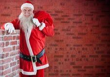 Santa Claus med gåvasäckanseende bredvid en lampglas Royaltyfri Foto