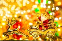 Santa Claus med gåvor på bilen med julhjortar, på bokehbackg arkivbild