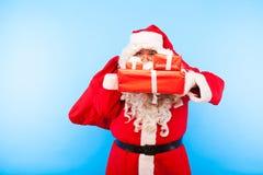 Santa Claus med gåvor på händer på blå bakgrund royaltyfri bild