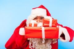 Santa Claus med gåvor på händer på blå bakgrund arkivfoton