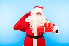 Santa Claus med gåvor på händer på blå bakgrund fotografering för bildbyråer