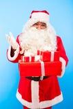 Santa Claus med gåvor på händer på blå bakgrund arkivbilder