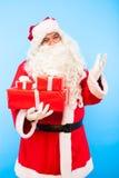 Santa Claus med gåvor på händer på blå bakgrund royaltyfria bilder