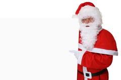 Santa Claus med hatten som pekar på jul på det tomma banret med Arkivfoto
