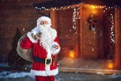 Santa Claus med klockan och säcken av gåvor Fotografering för Bildbyråer