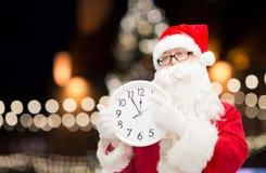 Santa Claus med klockan som pekar fingret till tolv Royaltyfria Foton