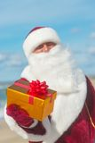 Santa Claus med många guld- gåvor som kopplar av på stranden Arkivbild