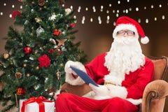 Santa Claus med minnestavlaPC och julträdet Royaltyfria Bilder
