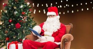 Santa Claus med minnestavlaPC och julträdet Royaltyfri Foto