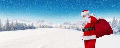 Santa Claus med panorama- alpint vinterlandskap Fotografering för Bildbyråer