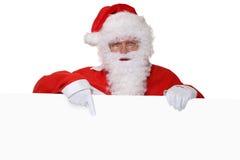 Santa Claus med skägget som pekar på jul på tom banerintelligens Arkivbilder