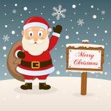 Santa Claus med tecknet för glad jul Fotografering för Bildbyråer