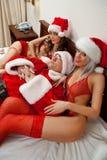 Santa Claus med två sexiga flickor Arkivfoto