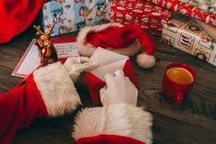 Santa Claus med vita handskar som rymmer ett kuvert på hans trätabell med gåvor Arkivfoto