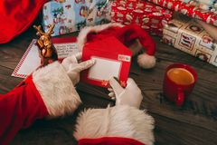 Santa Claus med vita handskar som rymmer ett kuvert på hans trätabell med gåvor Royaltyfria Foton