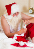 Santa Claus mending his socks Stock Photo
