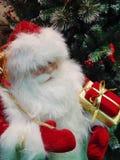 Santa Claus met een gift-doos bij de Kerstboom De achtergrond van het Kerstmisspeelgoed Royalty-vrije Stock Foto