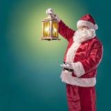 Santa Claus met een lantaarn op een turkooise achtergrond Stock Foto's