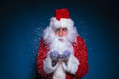 Santa Claus met glazen die sneeuw blazen Royalty-vrije Stock Afbeeldingen