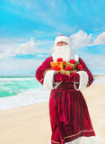 Santa Claus met vele gouden giften op overzees strand Stock Afbeelding