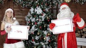 Santa Claus met zijn kleindochter, kondigt de laatste kans van 70% aan stock video
