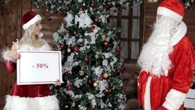 Santa Claus met zijn nicht, kiest het percentage kortingen voor de wintervakantie stock videobeelden