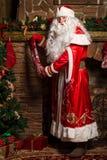 Santa Claus mettant des cadeaux dans des bas de Noël à la cheminée Images stock