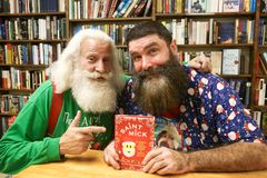 Santa Claus, Mick Foley. NEW YORK-OCT 19: Mick Foley R and Santa Claus at a book signing for `Saint Mick: My Journey From Hardcore Legend to Santa`s Jolly Elf` Stock Images