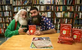 Santa Claus, Mick Foley. NEW YORK-OCT 19: Mick Foley R and Santa Claus at a book signing for `Saint Mick: My Journey From Hardcore Legend to Santa`s Jolly Elf` Royalty Free Stock Image