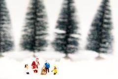 Santa Claus miniature avec l'homme de neige font l'heure heureuse pour des enfants le jour de Noël, Images libres de droits