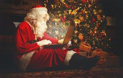 Santa Claus mit Computer vor Weihnachten stockbilder