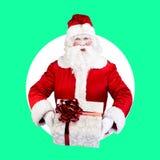Santa Claus mit dem Geschenk, das auf Farbweißem Grün aufwirft Stockfotografie