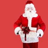 Santa Claus mit dem Geschenk, das auf rotem Hintergrund aufwirft Lizenzfreie Stockbilder