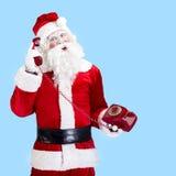 Santa Claus mit dem roten Telefon, das auf Blau aufwirft Stockfotografie