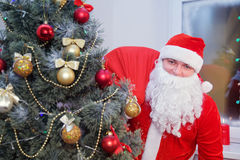 Santa Claus mit einer Tasche nahe dem Weihnachtsbaum Stockfotografie