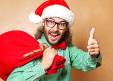 Santa Claus mit einer Tasche von den Geschenken, die Kamera betrachten und Si zeigen Lizenzfreie Stockbilder