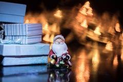 Santa Claus mit Geschenkbox auf dem Hintergrund des bunten bokeh in Form von Weihnachtsbäumen Stockbilder