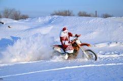 Santa Claus mit gespreizten Beinen auf dem Motocrossfahrrad Stockbild
