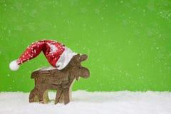 Santa Claus mit rotem Hut - hölzernes Rotwild auf grünem Weihnachten-backgr Lizenzfreies Stockfoto