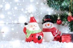 Santa Claus mit Schneemann und Schneefällen über Tannenbaum Stockfotos