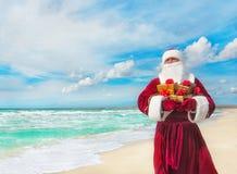 Santa Claus mit vielen goldenen Geschenken auf Seestrand Lizenzfreie Stockfotos