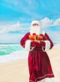 Santa Claus mit vielen goldenen Geschenken auf Seestrand Stockbild