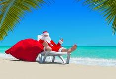 Santa Claus mit Weihnachtssack auf deckchair bei Palm Beach Lizenzfreie Stockfotos