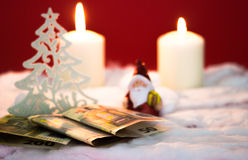 Santa Claus with money. Santa Claus with burning candles and money on red background Stock Images