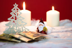 Santa Claus with money. Santa Claus with burning candles and money on red background Royalty Free Stock Photography