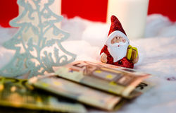 Santa Claus with money. Santa Claus with candles and money on red background Royalty Free Stock Images