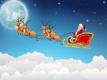 Santa Claus monta el vuelo del trineo del reno en el cielo Imagen de archivo