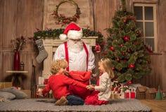 Santa Claus montrant des cadeaux de Noël Photographie stock libre de droits